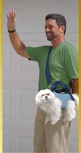 man carrying a dog as a purse